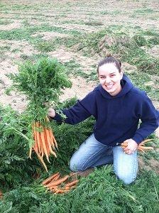 Kaylie holding fresh dug carrot